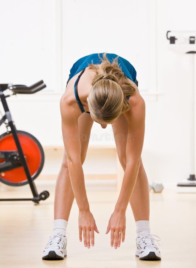 Mulher que exercita no clube de saúde fotografia de stock royalty free