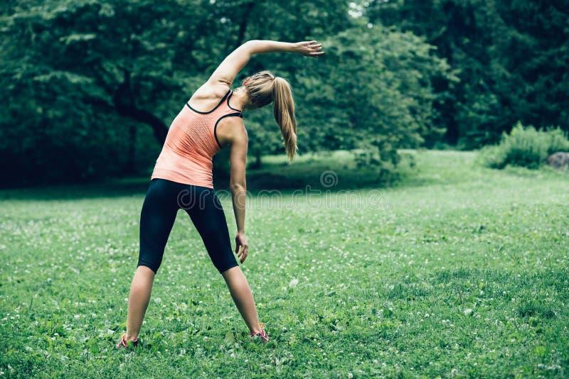 Mulher que exercita no gramado da floresta da natureza na manhã imagem de stock royalty free