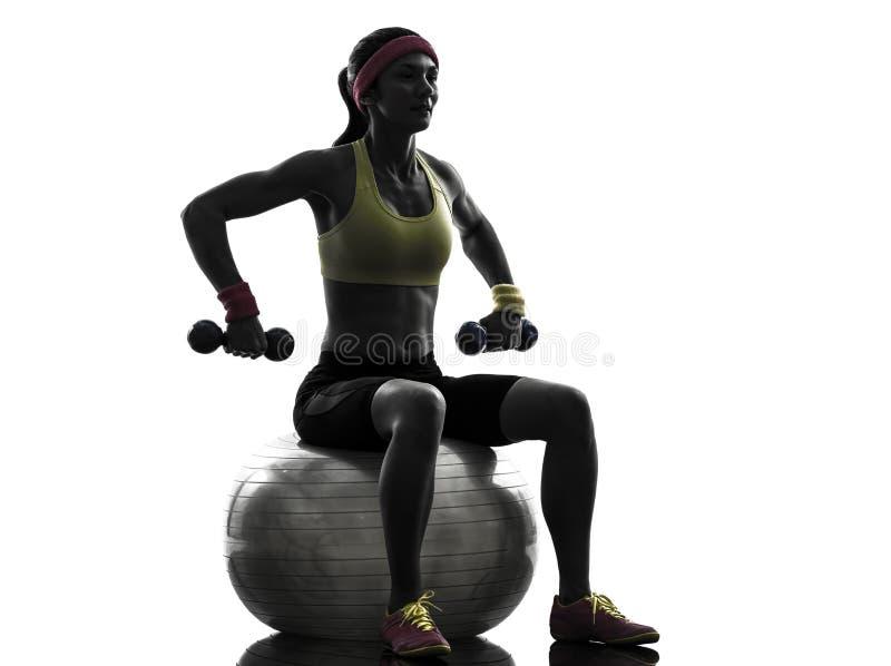 Mulher que exercita a silhueta do treinamento do peso da bola da aptidão fotografia de stock