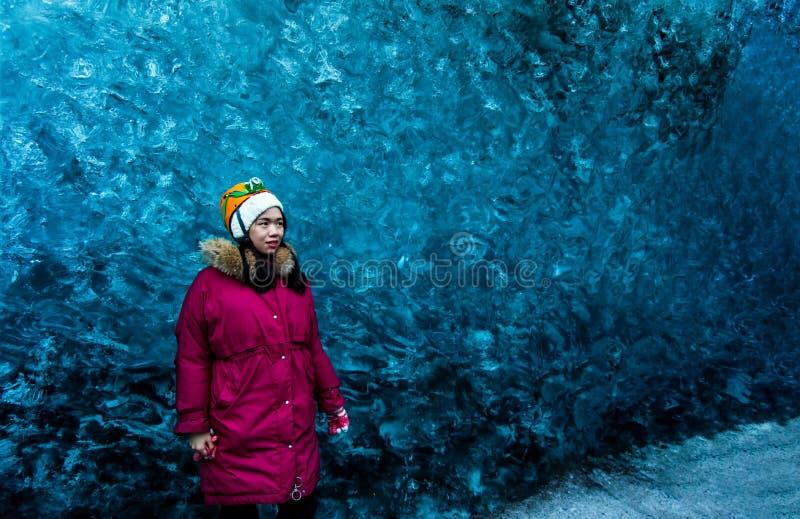 Mulher que explora a caverna de gelo azul em Islândia imagens de stock royalty free