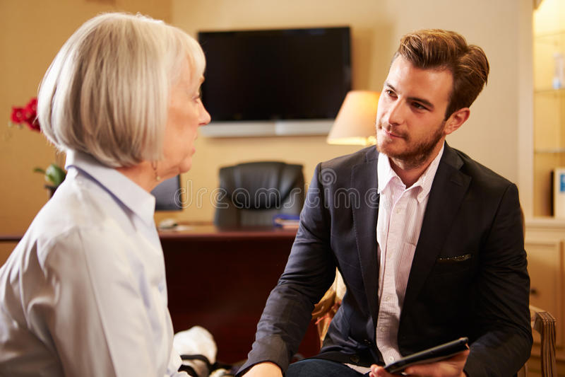Mulher que fala ao conselheiro masculino que usa a aba de Digitas imagens de stock royalty free