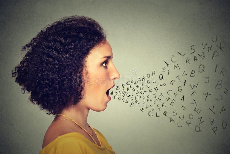 A mulher que fala com alfabeto rotula a saída de sua boca Conceito da inteligência de comunicação imagens de stock royalty free