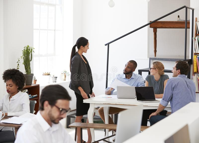 Mulher que fala com colegas em uma mesa no escritório de plano aberto imagem de stock royalty free