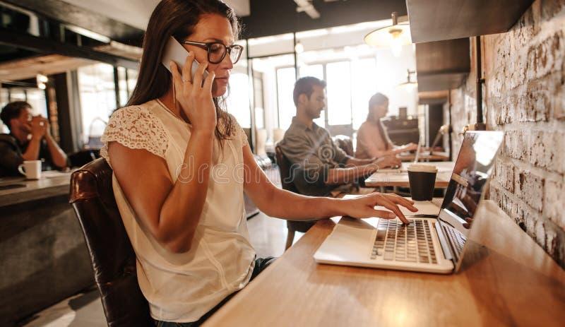 Mulher que fala com o cliente no telefone celular foto de stock