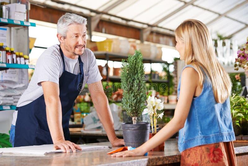 Mulher que fala com o vendedor no berçário imagens de stock royalty free