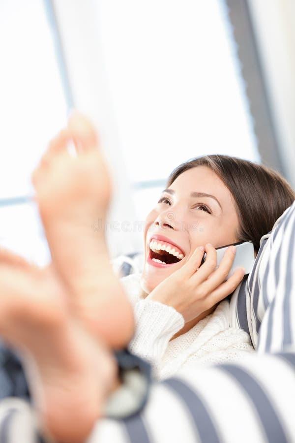 Mulher que fala e que ri no telefone esperto fotografia de stock