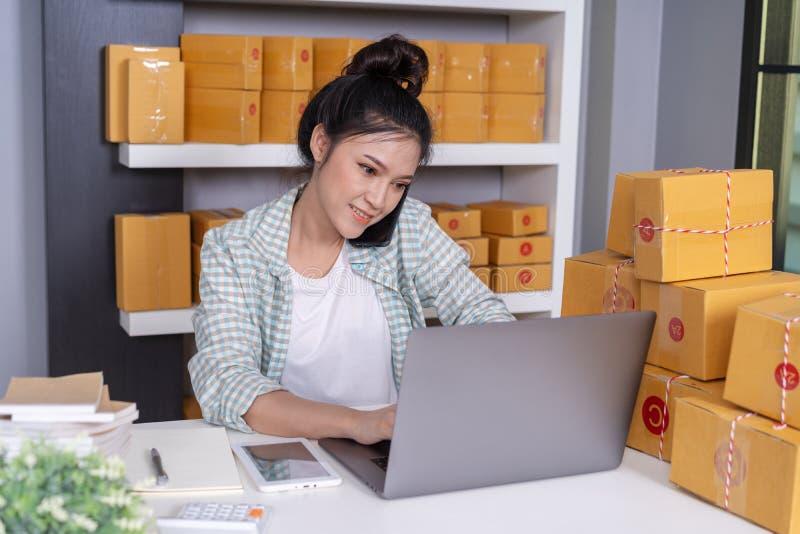 Mulher que fala no portátil do smartphone e do computador do uso a vender o produto em linha do escritório domiciliário imagem de stock