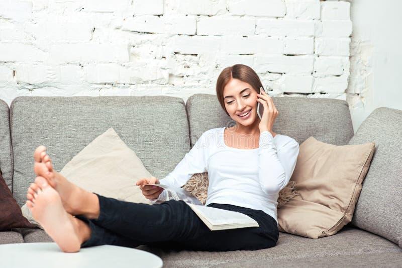 Mulher que fala no telefone celular que encontra-se no sofá imagens de stock