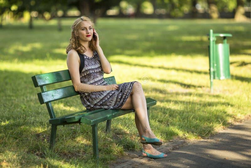 mulher que fala no telefone celular que senta-se em um banco no parque foto de stock royalty free