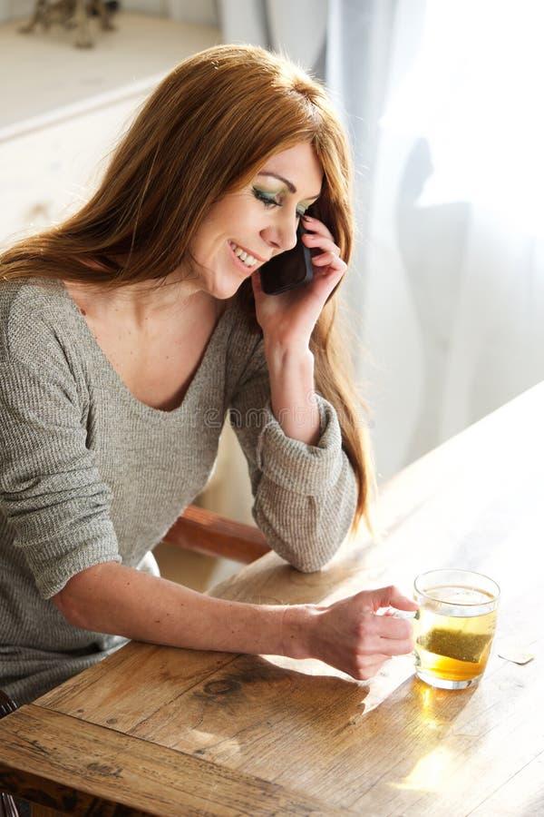 Mulher que fala no telefone e que come o chá em casa foto de stock