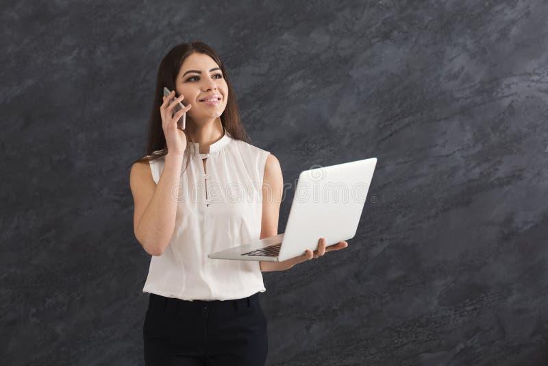 Mulher que fala no telefone e que guarda o portátil fotografia de stock royalty free