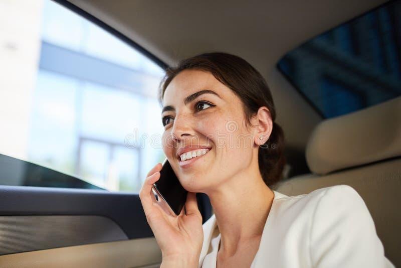 Mulher que fala por Smartphone no carro foto de stock royalty free