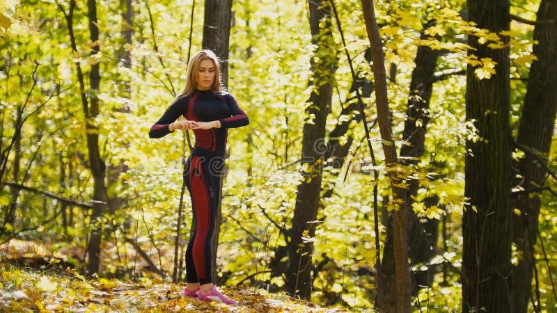 A mulher que faz a aptidão exercita exterior Esticão fêmea na menina magro da floresta do outono no exercício imagem de stock