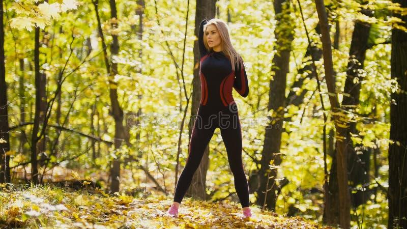 A mulher que faz a aptidão exercita exterior Fêmea que estica seu lombo na menina magro da floresta do outono no exercício fotos de stock