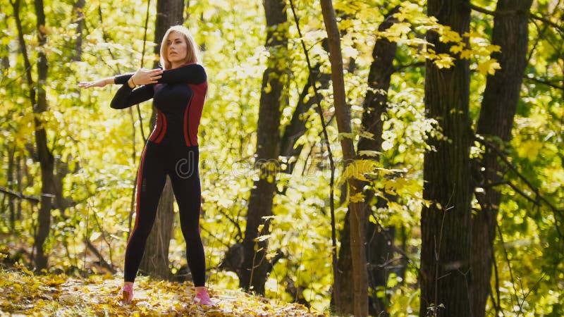 A mulher que faz a aptidão exercita exterior A fêmea que estica seus ombros na menina magro da floresta do outono em dá certo - o imagens de stock