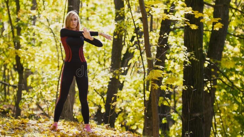 A mulher que faz a aptidão exercita exterior A fêmea que estica seus ombros na menina magro da floresta do outono em dá certo - o foto de stock