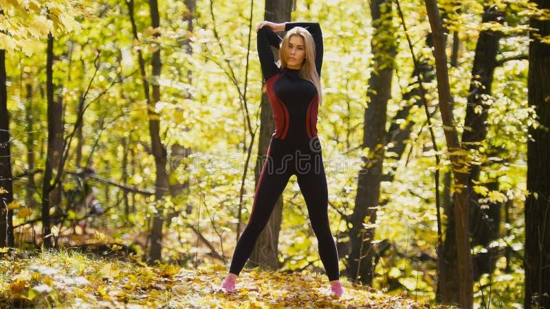 A mulher que faz a aptidão exercita exterior Fêmea que estica seus ombros na menina magro da floresta do outono no exercício foto de stock royalty free