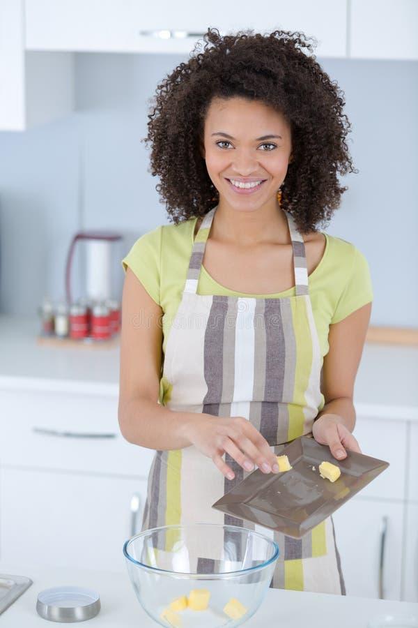 Mulher que faz bolos na cozinha fotografia de stock