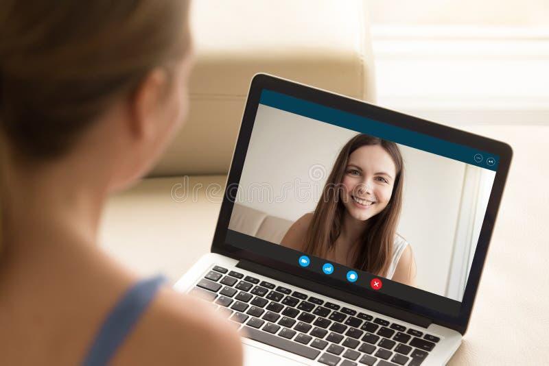 Mulher que faz a chamada video ao amigo fêmea no portátil fotografia de stock