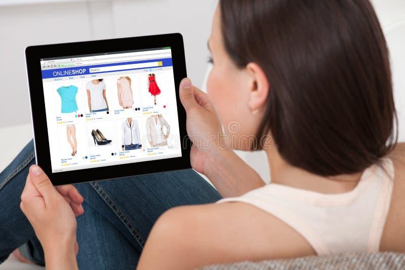 Mulher que faz a compra em linha na tabuleta de Digitas imagens de stock royalty free