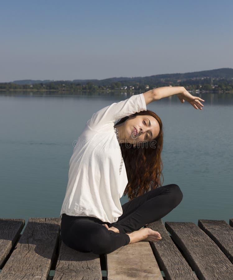 Mulher que faz a curvatura lateral assentada durante a ioga fora imagem de stock