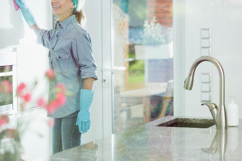 Mulher que faz deveres da limpeza da casa imagem de stock