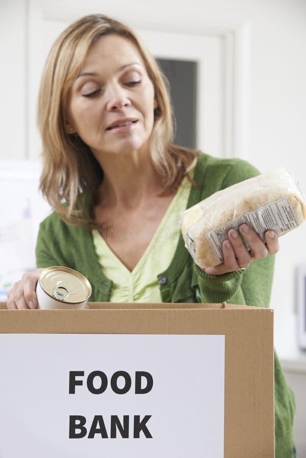 Mulher que faz a doação ao banco alimentar imagens de stock