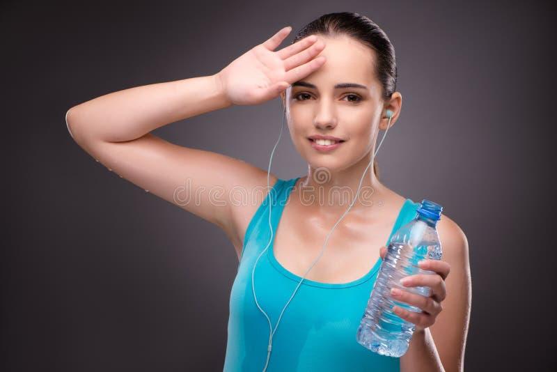 A mulher que faz esportes com a garrafa da água fresca foto de stock