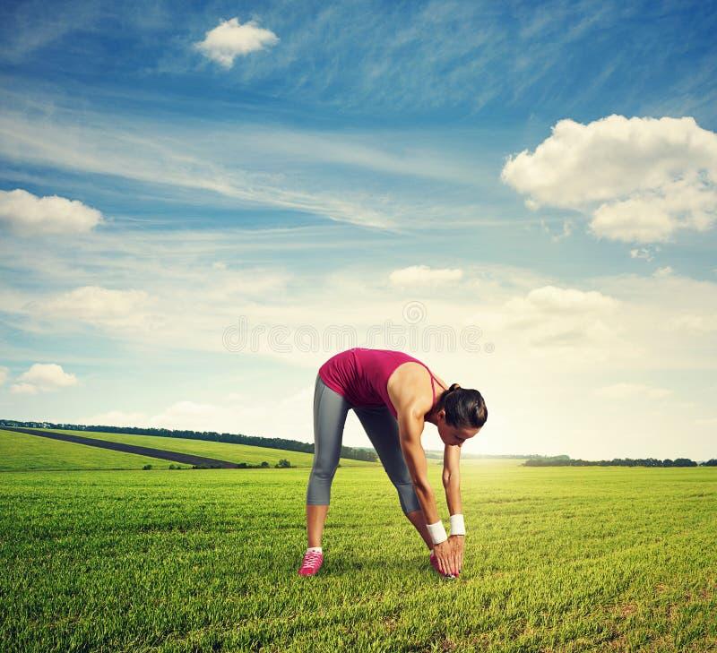 Mulher que faz esticando exercícios em exterior foto de stock royalty free