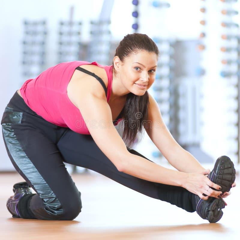 Mulher que faz esticando exercícios no gym foto de stock royalty free