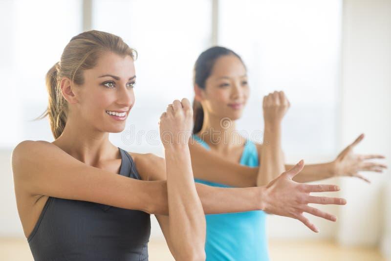 Mulher que faz esticando o exercício com amigo fêmea fotografia de stock royalty free