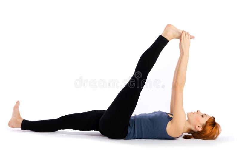 Mulher que faz esticando o exercício da ioga fotos de stock