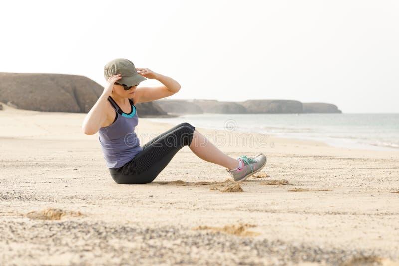 Mulher que faz estiramentos do torso pela praia foto de stock