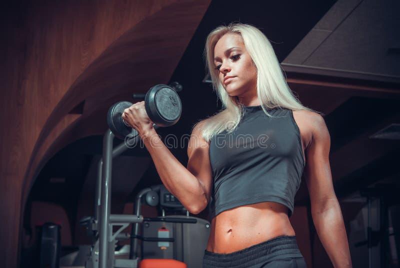 Mulher que faz exercícios com peso no gym fotos de stock royalty free