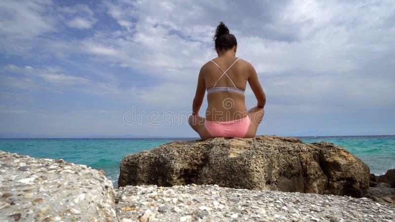 Mulher que faz exercícios da ioga na praia imagens de stock royalty free