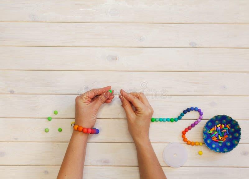 Mulher que faz grânulos coloridos Argila do polímero Fundo do wo branco imagem de stock royalty free