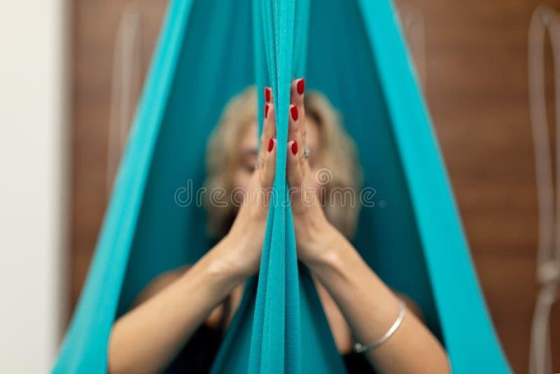 Mulher que faz a ioga da mosca que estica exercícios no gym Estilo de vida do ajuste e do bem-estar imagens de stock royalty free