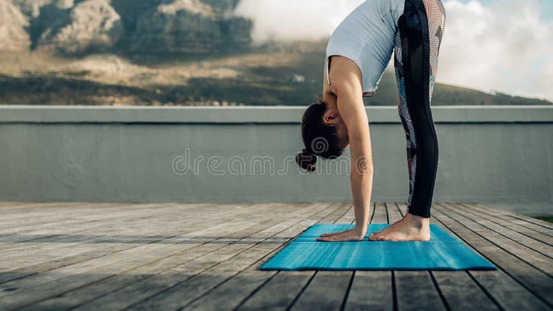 Mulher que faz a ioga exterior foto de stock