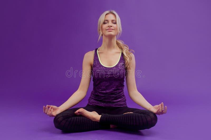Mulher que faz a ioga Mulheres desportivas novas em um fundo roxo imagem de stock royalty free