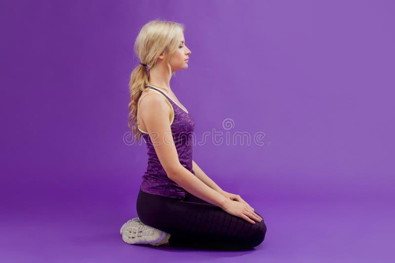 Mulher que faz a ioga Mulheres desportivas novas em um fundo roxo Relaxa, senta-se lateralmente imagens de stock royalty free