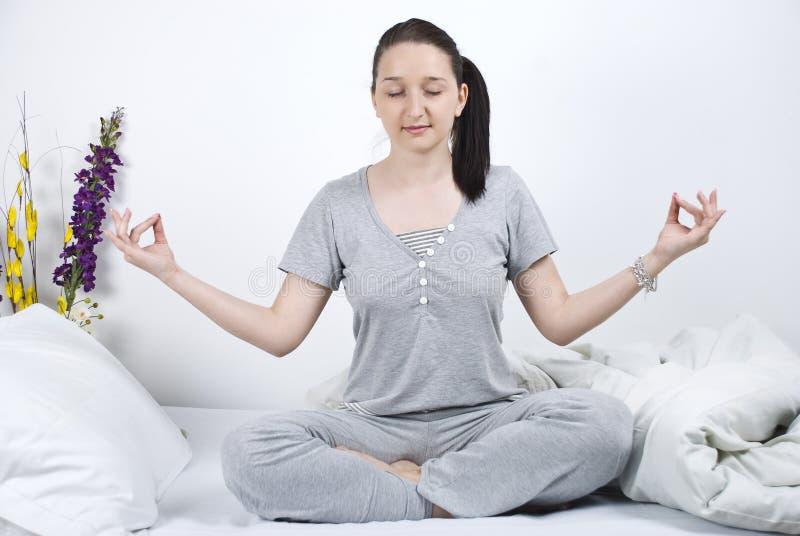 Mulher que faz a ioga na cama fotos de stock