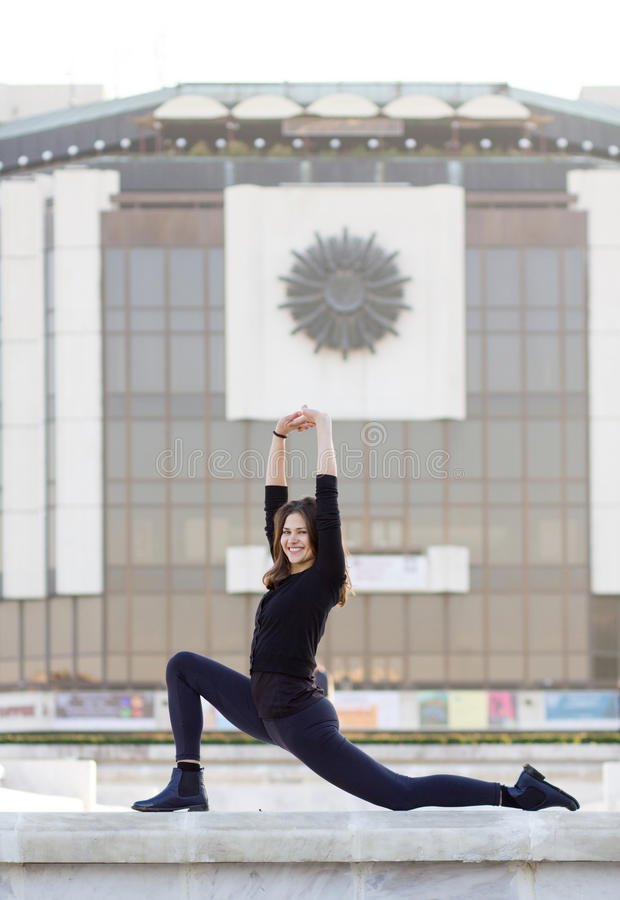 Mulher que faz a ioga na cidade imagem de stock