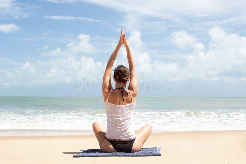 Mulher que faz a ioga na frente do oceano fotografia de stock royalty free