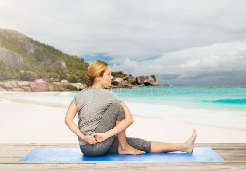 Mulher que faz a ioga na pose da torção na praia fotografia de stock
