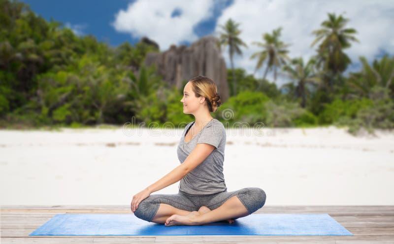 Mulher que faz a ioga na pose da torção na praia fotografia de stock royalty free