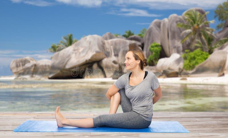 Mulher que faz a ioga na pose da torção na praia foto de stock royalty free