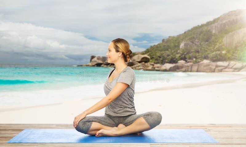 Mulher que faz a ioga na pose da torção na praia imagens de stock