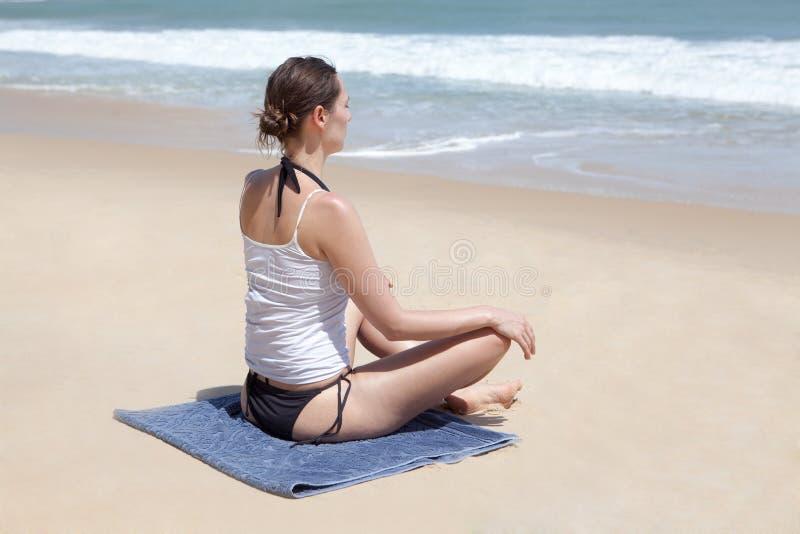 Mulher que faz a ioga na praia foto de stock royalty free