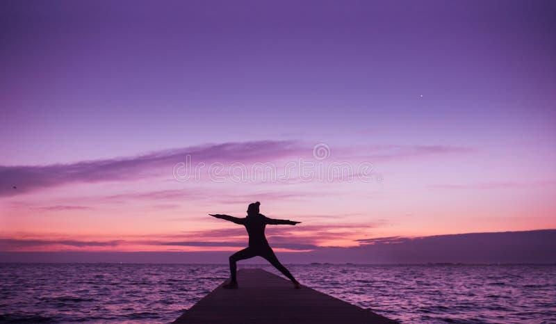 Mulher que faz a ioga na praia no surise foto de stock