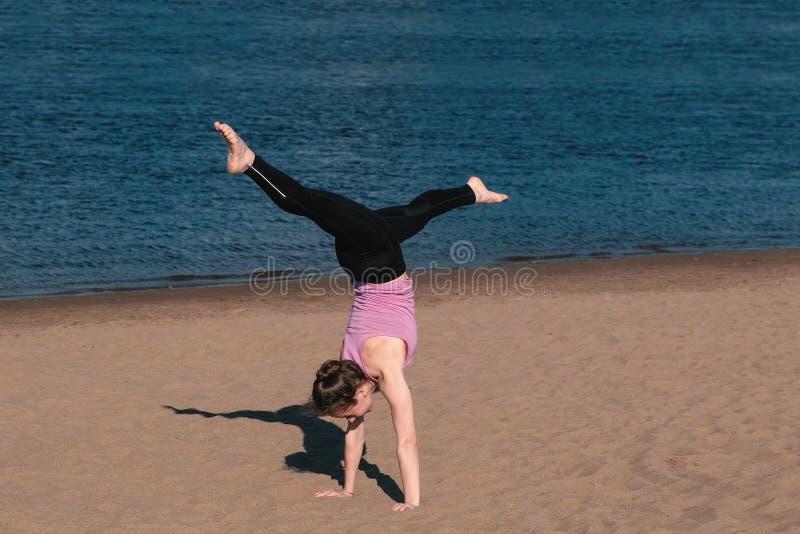 Mulher que faz a ioga na praia pelo rio na cidade Vista bonita handstand fotos de stock